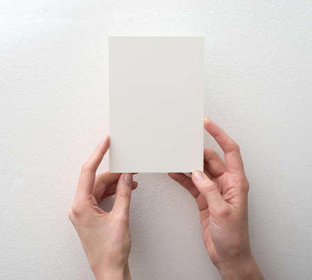 hand holding paper: hand holding blank card on white background