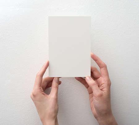 gente saludando: mano que sostiene la tarjeta en blanco sobre fondo blanco