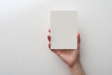personas saludandose: mano que sostiene la tarjeta en blanco sobre fondo blanco