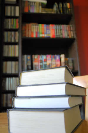 scholarly: Stack of books on a table with book shelf in the background Stock Photo
