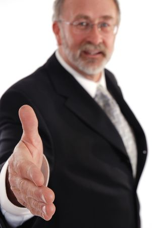 hand: Senior businessman holding out hand for a hand shake. Focus on hand Stock Photo