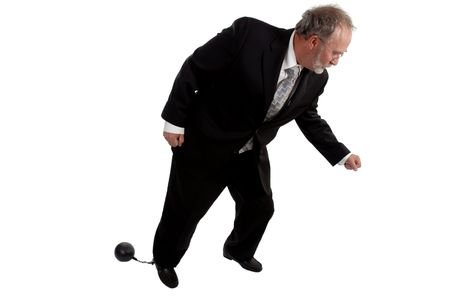 Businessman tring to move with a ball and chain attached to his leg  photo