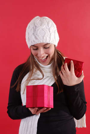 Beautiful young girl looking surprised opening a gift Stock Photo - 2020331