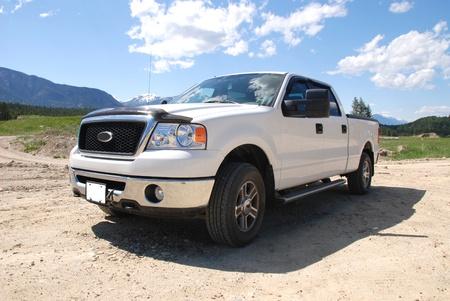 camioneta pick up: Pick-up en un camino de tierra en las montañas.