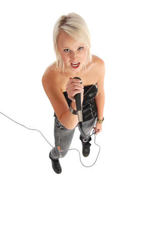 A blond girl singing into a microphone. Stock Photo - 10633176