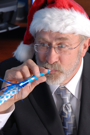 A senior businessman at a Christmas party, wearing a Santa hat and blowing a party blower photo