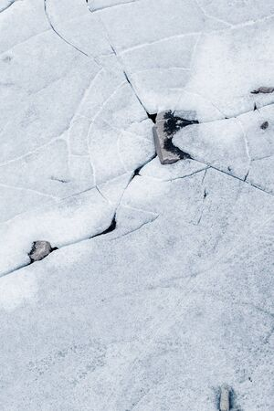 interstice: ice background texture with a long crack and rock Stock Photo