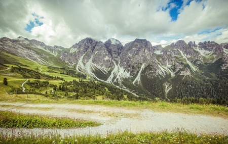 Mountain landscape with trail, green meadow and forest, Austrian Alps
