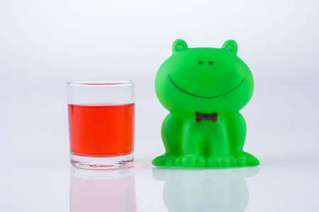 lovely green frog and red water in glass