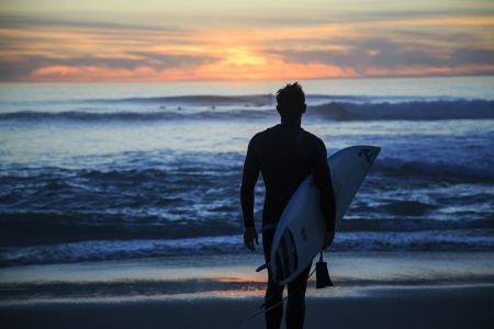 San Diego, California, USA - March 02, 2013  A surfer enjoying sunset at Windansea Beach, La Jolla, San Diego  Windansea Beach is one of the most famous places for surfing in San Diego, California, USA
