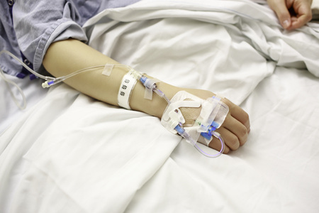 Patient With IV Lines in Hospital Bed