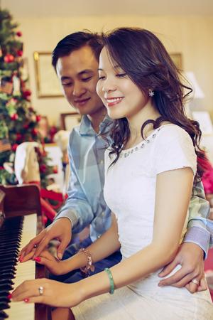 행복 한 젊은 커플 크리스마스에 함께 피아노를 연주 스톡 콘텐츠
