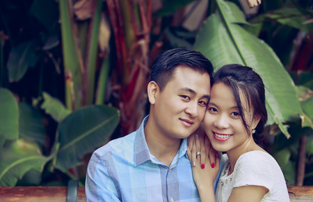 Portrait of happy young couple sitting in a garden Reklamní fotografie