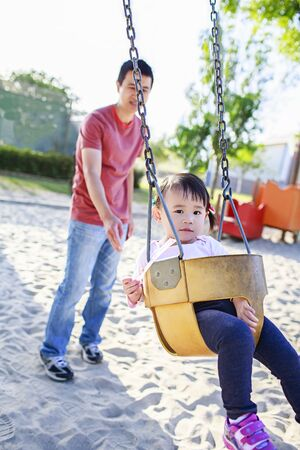 Toddler girl playing outdoor with father