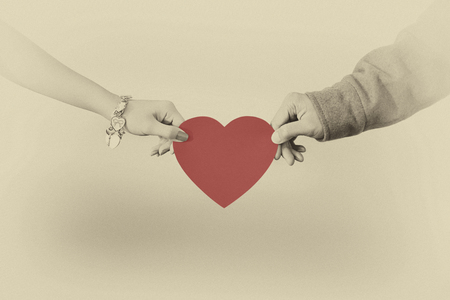 Man and woman hands holding a heart shape
