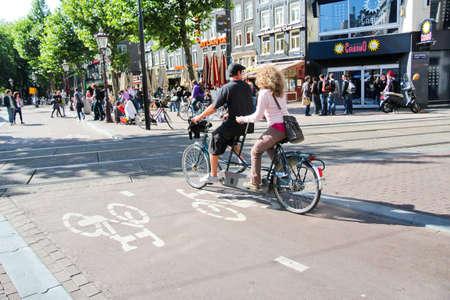 Pareja de montar en tándem en un carril bici de Rembrandt lugar, Amsterdam Editorial