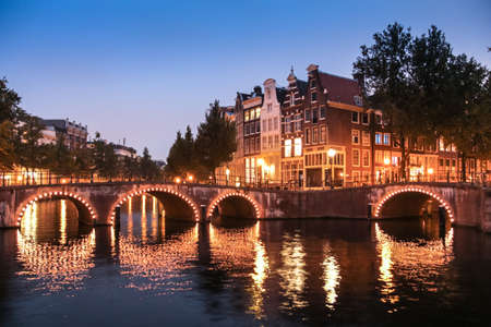 Famous corner of Keizersgracht and Leidsegracht canals and his illuminated bridges at night in Amsterdam  Archivio Fotografico