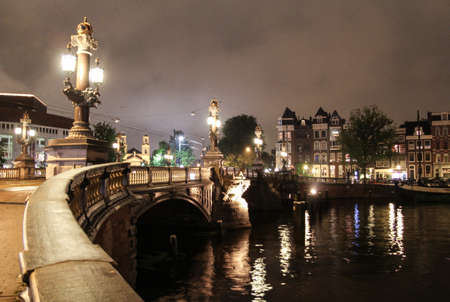 amstel: Famous bridge Blauwbrug illuminated at night over the Amstel river in Amsterdam