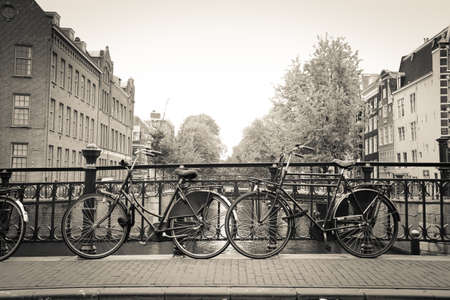 Các cặp vợ chồng của xe đạp màu đen cũ trong một cây cầu bắc qua con kênh ở Amsterdam