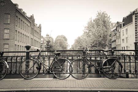 Pary starych czarnych rowerach w moście nad kanałem w Amsterdamie