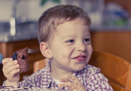 Little boy eating a piece of brownie with a cute smile photo