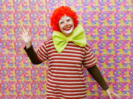 Funny clown with makeup and party background color photo