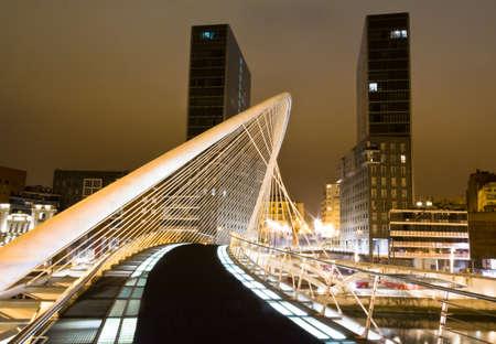 Vista nocturna del puente Zubizuri y torres de Isozaki en el fondo, en Bilbao, España, el 02 de abril de 2012 El puente Zubizuri fue diseñado por el arquitecto español Santiago Calatrava, y las torres por el arquitecto japonés Arata Isozaki Editorial