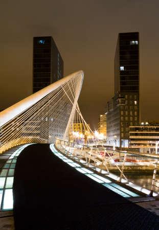 Nightview of Zubizuri bridge and Isozaki towers in the background, in Bilbao, Spain, on April 02, 2012  The Zubizuri bridge was designed by spanish architect Santiago Calatrava, and the towers by japanese architect Arata Isozaki