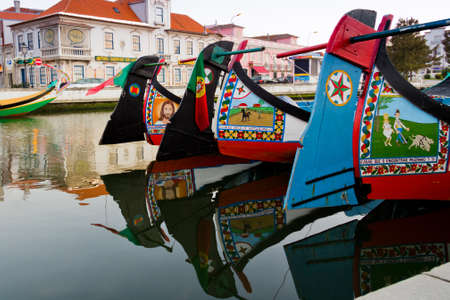 View of handmade paints in traditional moliceiro boats, in a canal of Aveiro, Portugal