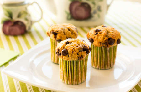 Three chocolate chip muffins on white plate and green striped tablecloth at breakfast photo