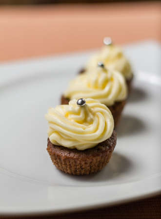 Three chocolate cupcakes with silver sprinkles on top, on white plate and fabric tablecloth Stock Photo - 17031813