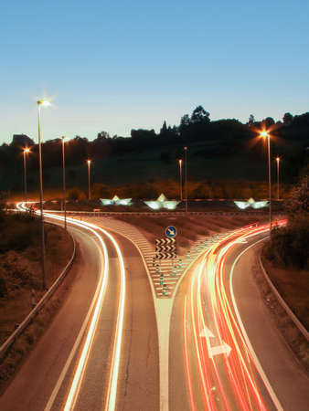 Car light trails on the road at night and illuminated paper boats in a roundabout in background photo