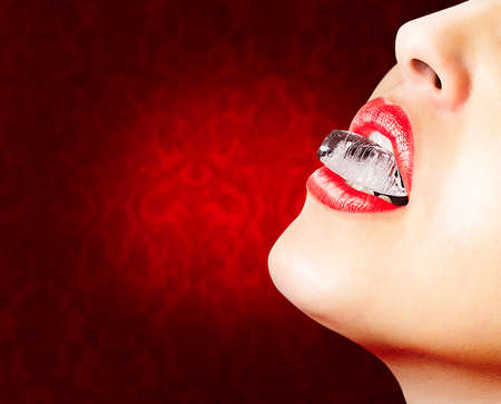 Closeup of sensual lips with red lipstick and an ice cube photo