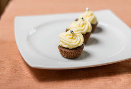 Three chocolate cupcakes with silver sprinkles on top, on white plate and fabric tablecloth photo