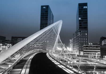 Bilbao, Hiszpania - 02 kwietnia Nightview Zubizuri Bridge i wieże Isozaki w tle, w Bilbao, w Hiszpanii, dnia 02-kwiecień 2012 r. Zubizuri Most został zaprojektowany przez hiszpańskiego architekta Santiago Calatrava, a wieże przez japońskiego architekta Arata Isozaki Publikacyjne
