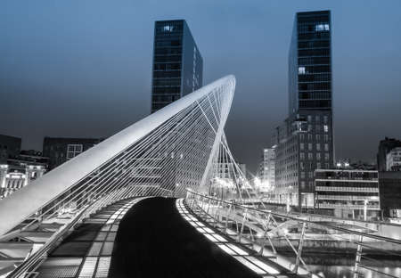 BILBAO, SPAIN - APRIL 02 Nightview of Zubizuri bridge and Isozaki towers in the background, in Bilbao, Spain, on April 02, 2012  The Zubizuri bridge was designed by spanish architect Santiago Calatrava, and the towers by japanese architect Arata Isozaki