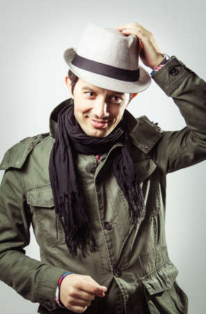 Portrait of handsome trendy young man wearing hat and scarf on grey background photo