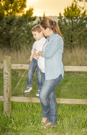 Pregnant mother sitting her cute son on a wooden fence in a field at sunset photo