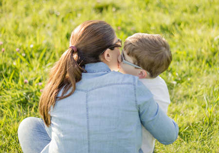 mom kiss son: Back view of cute son kissing to his mother sitting in a sunny field