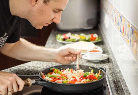 tortilla de maiz: Handsome Man cocinar las verduras y el pollo para una comida mexicana en una sartén negro