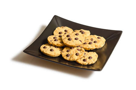 chocolate chip cookie: Pile of chocolate chip cookies on a square black plate, isolated on white background Stock Photo