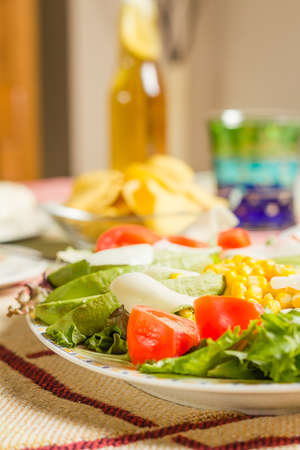 fajita: Closeup of traditional mexican food in a table, with a plate of fresh salad and a  bowl of nachos Stock Photo