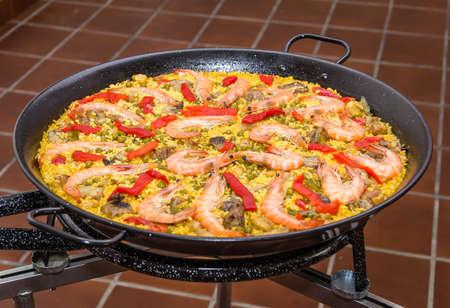 Primer plano de paella española tradicional cocinado en una sartén, con arroz amarillo y mariscos