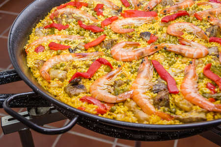 Closeup of traditional spanish paella cooked in a pan, with yellow rice and seafood photo