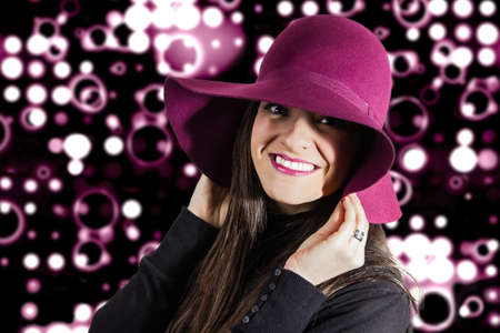 Portrait of beautiful young girl with a garnet hat on her head, in front of spotlights background photo