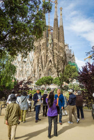 initiated: BARCELONA, SPAIN - JUNE 01 People photograph the Sagrada Familia cathedral, designed by Antoni Gaudi, in Barcelona, Spain, on June 01, 2013  It is a church with a modernist architecture, initiated in 1882, and still under construction