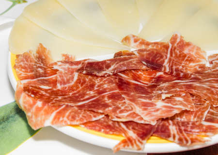 cured ham: Closeup of typical spanish tapa, with slices of serrano ham and manchego cheese served in a plate Stock Photo