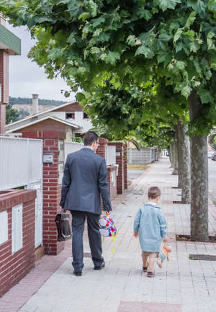 Business father and little cute son walking on the street to the school photo