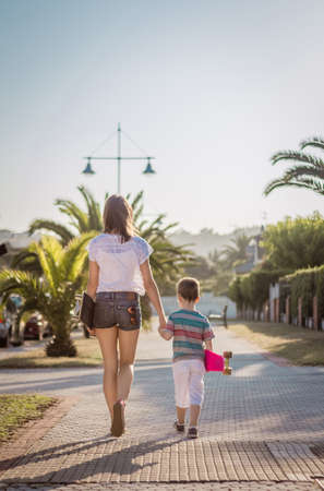Beautiful young girl and cute kid walking with a skateboards outdoor on summer photo