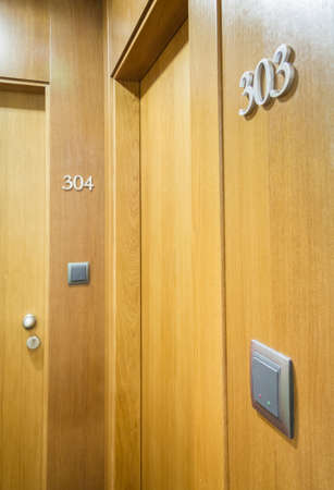 Closeup of wooden door with electronic key and room number in hotel photo